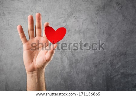 Be my Valentine, Valentines day concept. Man holding red paper heart in his hand - stock photo