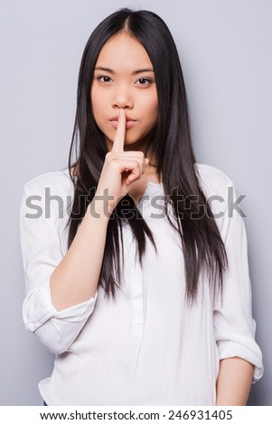 Be quiet! Attractive young Asian woman looking at camera and holding finger on lips while standing against grey background - stock photo