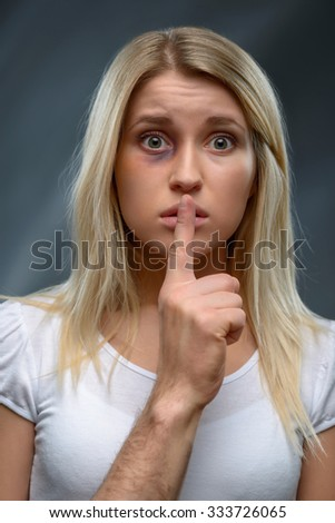 Be silent. Portrait of young beaten desperate girl holding finger near her mouth and keeping silence while standing isolated on grey background - stock photo
