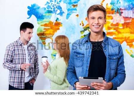 Be student is cool! Confident young man holding tablet  and looking at camera with smile while his colleagues talking in the background. - stock photo