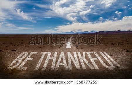 Be Thankful written on desert road - stock photo