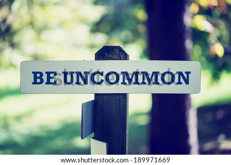 Be uncommon signpost in beautiful woodland with a vintage instagram style filter effect. - stock photo