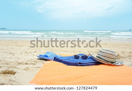 beach accessories close up at sand beach against blue sea - stock photo
