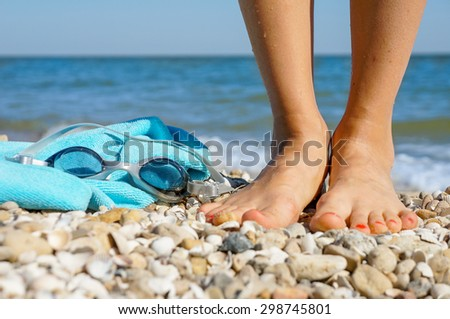 Beach accessories. Concept of summer vacations, focus on toes and goggles - stock photo