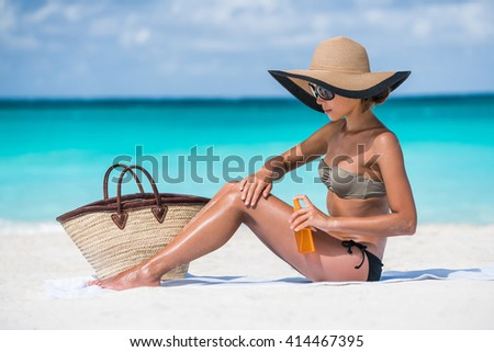 Beach accessories essentials for a summer holiday tropical vacation: sunglasses, straw hat, tote bag, towel, sunscreen. Sexy bikini woman applying sunblock sun protection lotion on Caribbean travel. - stock photo