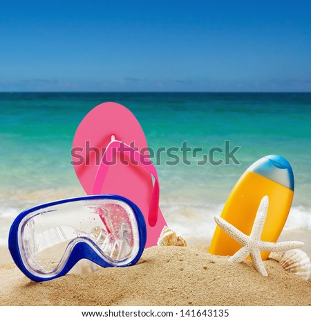 beach accessories in the sand against the sea landscape - stock photo
