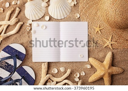 beach accessories on sand and empty notebook - stock photo