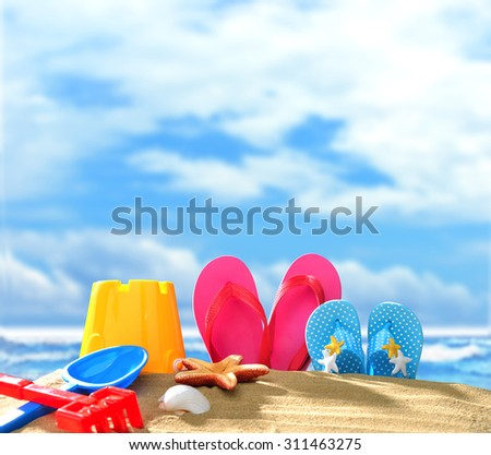 Beach accessories on sandy beach with blue sea and sky background