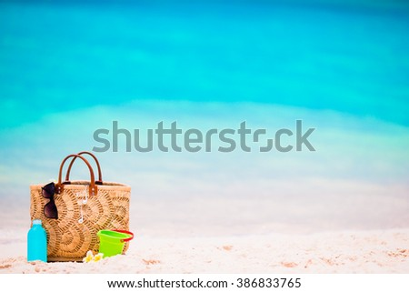 Beach accessories - straw bag, suncream bottle and red sunglasses on the beach - stock photo