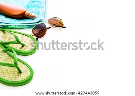 Beach accessories. Summer shoes and towel with sunglasses and suntan lotion on a white background - stock photo