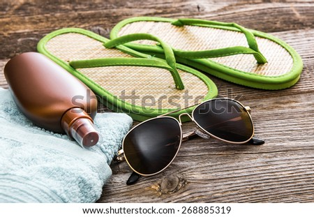 Beach accessories. Summer shoes and towel with sunglasses and suntan lotion on a wooden background - stock photo