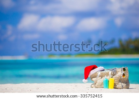 Beach accessories with Santa Hat on white tropical beach - stock photo