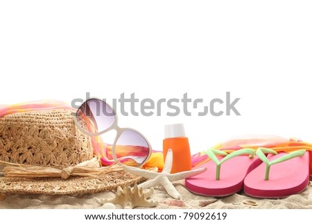 Beach accessories with straw hat,sun glasses,shawl and flip flops on sand. - stock photo