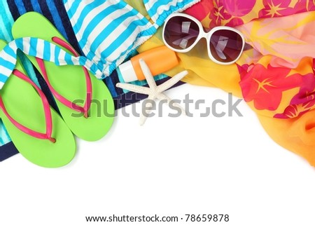 Beach accessories with swimming suit,sun glasses,shawl and flip flops on white background. - stock photo