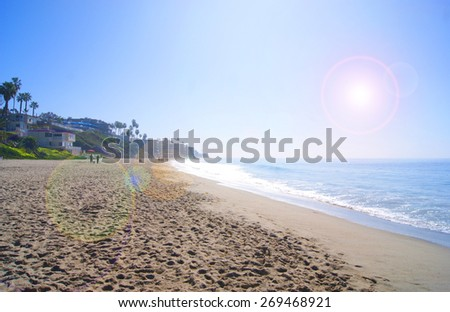 beach and ocean with bright sun flare - stock photo