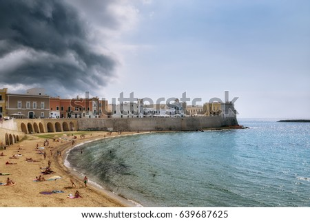 Beach and old town of Gallipoli under clouds of brewing thunderstorm, selective focus, Puglia, Italy