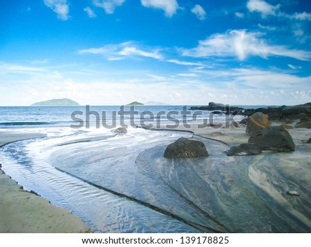 Beach and river under blue sky - stock photo