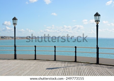 Beach and seafront at Worthing, West Sussex, England. Viewed from end of pier. With lamps and railings