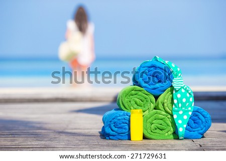 Beach and summer accessories concept - colorful towels, swimsuit and sunsblock - stock photo