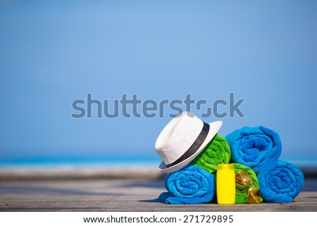Beach and summer vacation accessories concept - close-up of colorful towels, hat and sunscreen  - stock photo