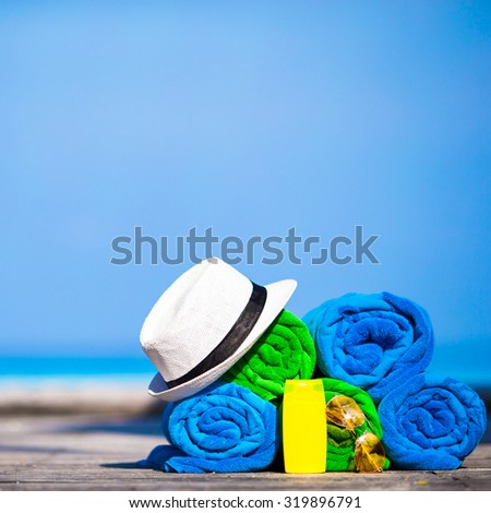 Beach and summer vacation accessories concept - close-up of colorful towels, hat, swimming goggles and sunblock - stock photo
