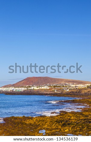 beach and village  of Playa Blanca with the volcano montana Roja in the background - stock photo