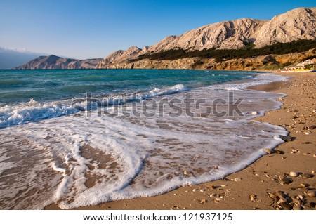Beach at Baska with foam sea wave in Krk - Croatia - stock photo
