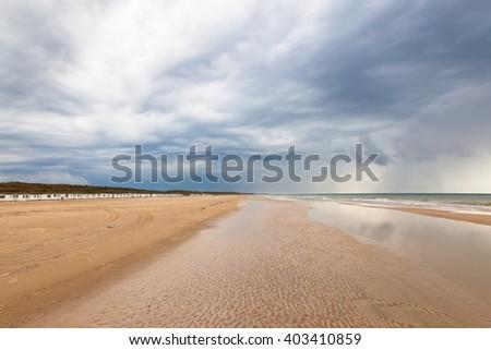 Beach at Lokken in Denmark with dark storm clouds - stock photo