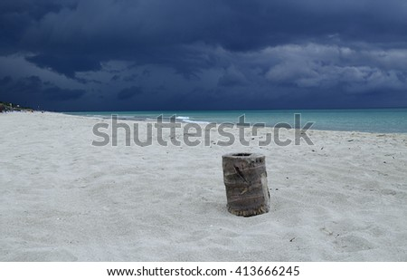 Beach at Varadero in Cuba just before a storm. In the foreground is the rest of the palm trunk. - stock photo