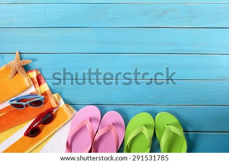 Beach background, flip flops, sunglasses, blue wood deck, copy space - stock photo