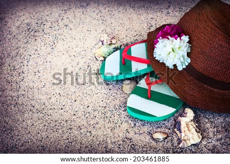 Beach background with copyspace, beach sand summer theme, straw hat with flowers and white and blue flip flops over sand texture - stock photo