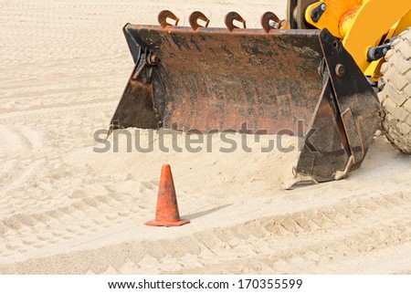 Beach backhoe industrial tractor shovel and sand close up. Heavy construction equipment vehicle digging in sand. Orange traffic cone. Tire tracks. Horizontal scene. - stock photo