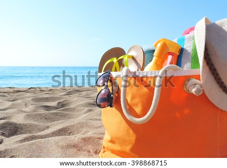 Beach bag and sea. Orange beach bag with hat, book, towel and other beach life stuff.