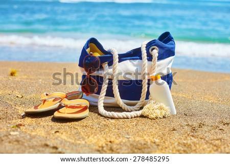 Beach bag, flip flops, sunscreen bottle and sunglasses on a Balinese beach - stock photo