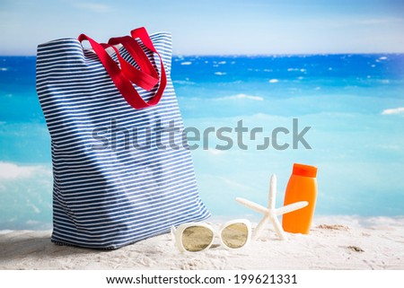 Beach bag, sunglasses, starfish and lotion - summer beach concept - stock photo