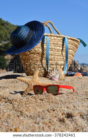 Beach bag with a book and a telephone and sunglasses accompanied by a sea star