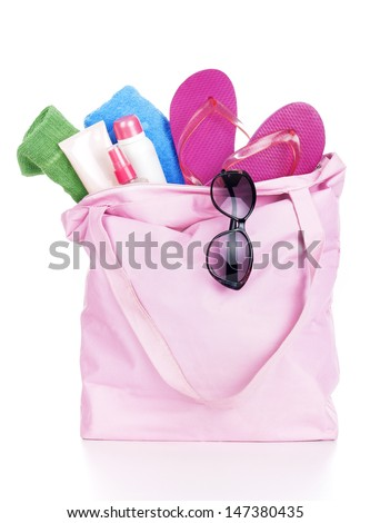 Beach bag with items for a day at the seaside on white background - stock photo