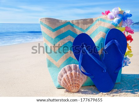 Beach bag with seashell and flip flops,