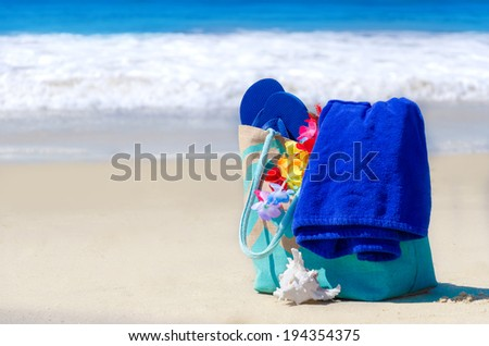 Beach bag with seashell, flip flops, and towel by the ocean