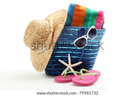 Beach bag with straw hat,towel,flip flops and sunglasses.Isolated on white background. - stock photo