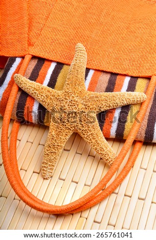 Beach bag with towel and starfish on a wooden background - stock photo