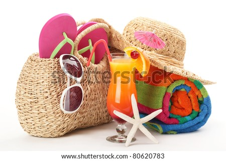 Beach bag with towel,flip flops, sunglasses and a glass of cocktail.Isolated on white background. - stock photo