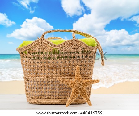 Beach bag with towel with ocean blur background - stock photo