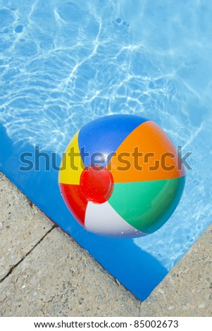 Beach ball floating in a blue pool