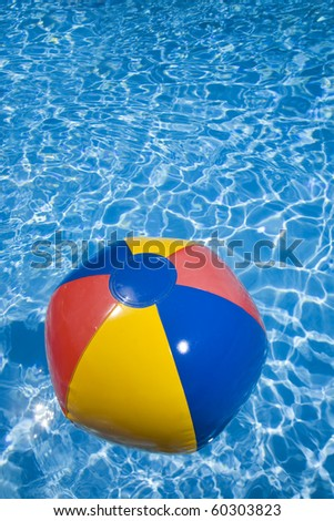 Beach ball in a sparkling blue swimming pool