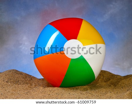 Beach Ball in the sand with blue background space for copy - stock photo