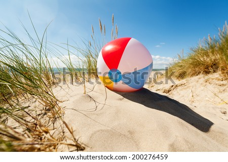 Beach ball resting in sand dune concept for childhood summer vacations, family holiday and healthy lifestyle - stock photo