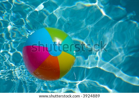 beach ball with green, blue, pink,yellow and orange with water ripples