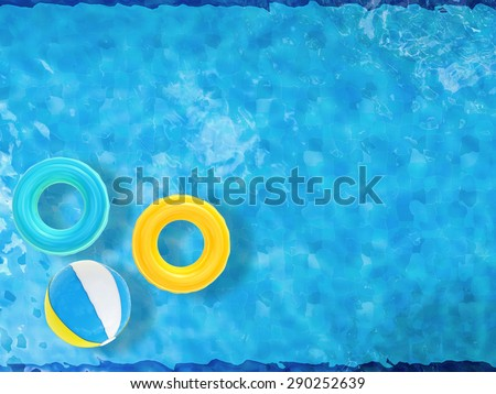 beach balls and swim rings floating on pool top view with blank space  - stock photo