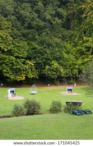 Beach Baskets or Strandkorbs, Swing Sunbeds and Wicker Sunbeds Amidst Greenery in Germany in Autumn